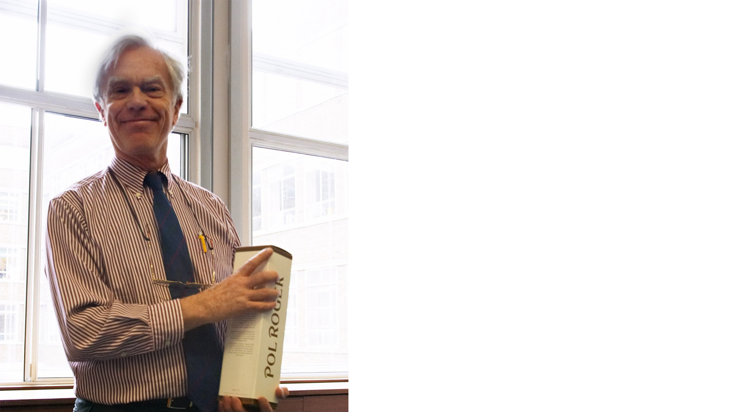Professor John Bridgwater in a red and white vertical striped shirt holding a boxed bottle of Pol Roger champagne